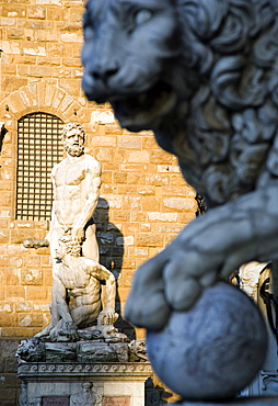 ITALY, Tuscany, Florence, The 1533 statue of Hercules and Cacus by Bandinelli seen through the legs of a stone lion outside the Loggia del Lancia or di Orcagna beside the Palazzo Vecchio in the Piazza della Signoria with a stone lion in the foreground