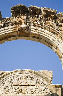 Turkey, Izmir Province, Selcuk, Ephesus, Detail of carved archway and wall relief against clear blue sky in ancient city of Ephesus on the Aegean sea coast