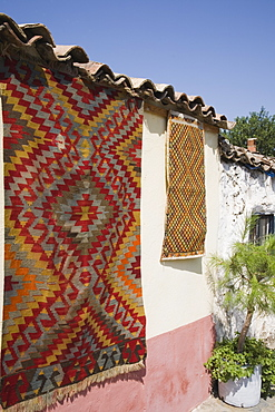 Turkey, Izmir Province, Selcuk, Kilim hanging up to dry in sun from wall of village house