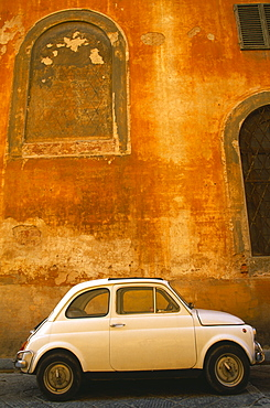 White Fiat 50 parked outside old building with faded ochre coloured plaster wall, Florence, Tuscany, Italy