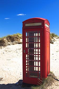 Traditional red British telephone box amongst the sand dunes of Studland Bay, Dorset, England, United Kingdom, Europe