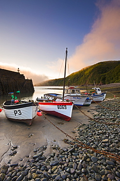 Fishing vessels beached at low tide in Clovelly harbour, Devon, England, United Kingdom, Europe