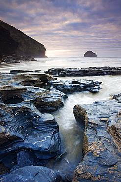 Eroded slate rocks on the beach at Trebarwith Strand, looking towards Gull Rock, Cornwall, England, United Kingdom, Europe