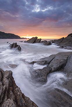 Colourful sunset sky above rocky Combe Martin on the north Devon coast, Exmoor National Park, Devon, England, United Kingdom, Europe