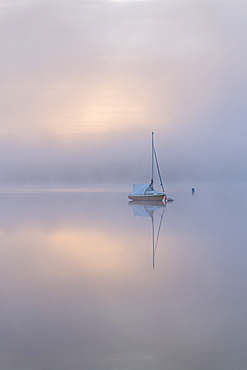 Sailing boat in misty conditions at dawn on Wimbleball Lake, Exmoor National Park, Somerset, England, United Kingdom, Europe