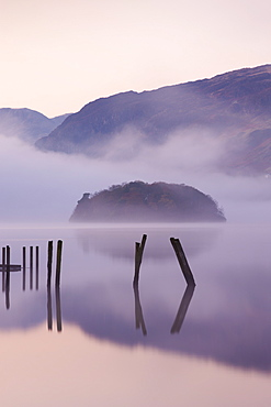 Old wooden jetty and St. Herbert's Island on Derwent Water at dawn on a misty autumn morning, Lake District National Park, Cumbria, England, United Kingdom, Europe - 799-359