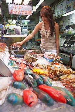 Woman looking at seafood in Makishi indoor market, Naha, Okinawa, Japan, Asia