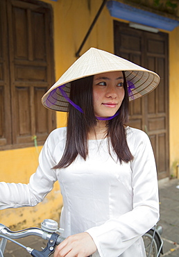 Woman wearing Ao Dai dress with bicycle, Hoi An, Quang Nam, Vietnam, Indochina, Southeast Asia, Asia