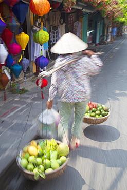 Woman carrying fruit along street, Hoi An, Quang Nam, Vietnam, Indochina, Southeast Asia, Asia