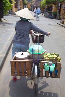Woman vendor pushing bicycle along street, Hoi An, Quang Nam, Vietnam, Indochina, Southeast Asia, Asia