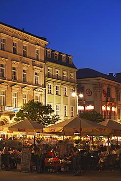Outdoor cafes in Main Market Square (Rynek Glowny) at dusk, Krakow, Poland, Europe