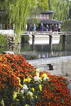 People crossing footbridge in Humble Administrator's Garden, UNESCO World Heritage Site, Suzhou, Jiangsu, China, Asia
