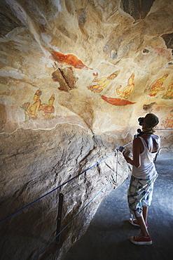 Tourist taking photos of ancient frescoes, Sigiriya, UNESCO World Heritage Site, North Central Province, Sri Lanka, Asia