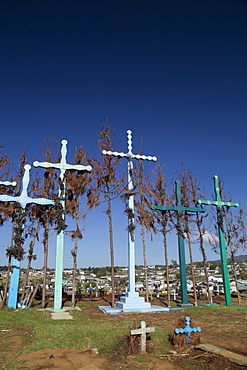 A series of tall crosses at the crest of the graveyard, boards represent doors to and from the grave, village of El Romerillo, Chiapas, Mexico, North America