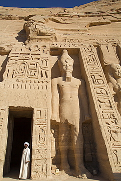 Local man at temple entrance, Ramses II statue on right, Hathor Temple of Queen Nefertari, Abu Simbel, UNESCO World Heritage Site, Egypt, North Africa, Africa