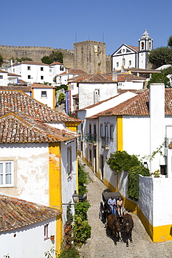 Horse drawn carriage, and overview of City with Medieval Castle in the background, Obidos, Portugal, Europe