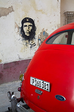 Vintage 1946 Ford with wall mural of Che Guevara, Centro Habana, Havana, Cuba, West Indies, Central America