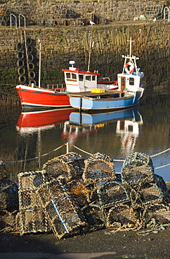 Lobster creels in the foreground with fishing boats in the harbour, Crail, Fife, Scotland, United Kingdom, europe