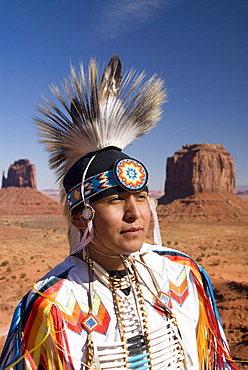 Navajo man dressed in a traditional costume, with Merrick Butte on the right and East Mitten Butte on the left in the background, Monument Valley Navajo Tribal Park, Utah, United States of America, North America