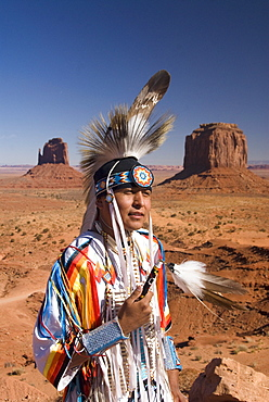 Navajo man in traditional costume, with Merrick Butte on the right and East Mitten Butte on the left in the background, Monument Valley Navajo Tribal Park, Utah, United States of America, North America