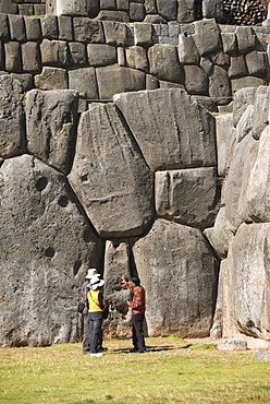 Guide talking to tourists at the Inca fortification of Sacsayhuaman, near Cuzco, Peru, South America