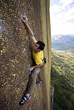A climber high on the big-wall route on the 450 metre monolith of Karimbony, Tsaranoro Massif, Andringitra National Park, Southern Madagascar, Africa