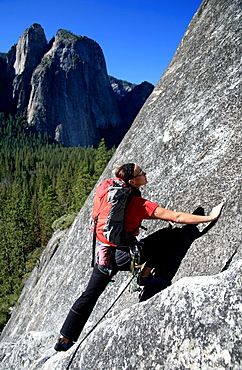 A woman climbing on cliffs opposite Cathedral Rock, near El Capitan, Yosemite Valley, California, United States of America, North America