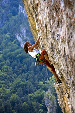 Rock climber tackles a very overhanging route on the famous limestone cliffs of the Gorge du Tarn in the Massif Central, near Millau and Rodez, south west France, Europe