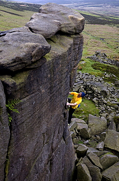 Climber makes a solo ascent of one of the thousands of classic outcrop climbs on the popular cliff of Stanage Edge, near Hathersage, Peak District, Derbyshire, England, United Kingdom, Europe