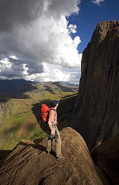 A climber looks up towards the 800 metre Tsaranoro Be (Big Tsaranoro) Monolith, Andringitra National Park, Southern Madagascar, Africa
