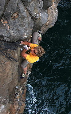 A climber deep water soloing above the sea on the limestone cliffs near St. Govan's Head, South Pembrokeshire, Pembrokeshire Coast National Park, Wales, United Kingdom, Europe