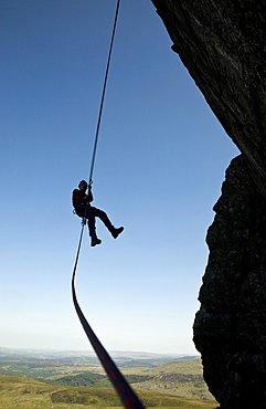 A climber abseiling from a cliff in the Ogwen Valley, Snowdonia, North Wales, United Kingdom, Europe
