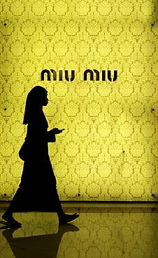 Muslim woman walking in front of the fashion store Miu Miu, Kuala Lumpur, Malaysia, Southeast Asia, Asia