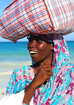 Woman carrying package on head, Zanzibar, Tanzania, East Africa, Africa