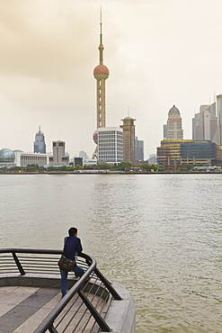 A man looking at the Oriental Pearl Tower and Pudong skyline across the Huangpu River from the Bund, Shanghai, China, Asia