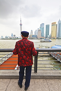 A man looking at the Pudong skyline from the Bund across the Huangpu River, Shanghai, China, Asia