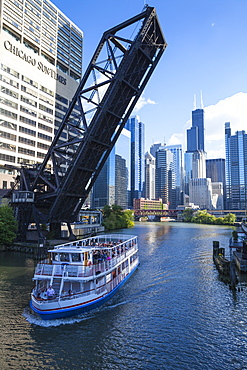 Tour boat passing under a raised disused railway bridge on the Chicago River, Downtown towers in the background, Chicago, Illinois, United States of America, North America