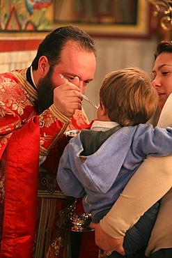 Greek Orthodox boy receiving the Eucharist, Thessaloniki, Macedonia, Greece, Europe