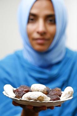 Muslim woman offering Ramadan pastries