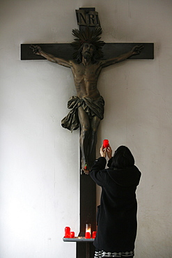 Woman offering candle and praying in front of Crucifix