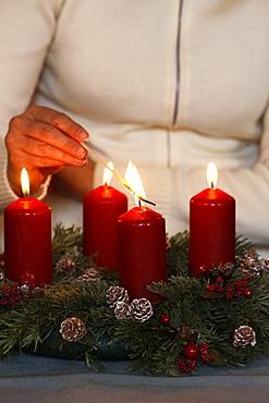 Woman lighting advent candles, Saint Nicolas de Veroce, Haute Savoie, France, Europe