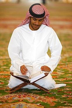 Muslim man reading the Koran, Sheikh Zayed Grand Mosque, Abu Dhabi, United Arab Emirates, Middle East