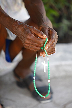 Haitian woman praying with prayer beads, Port au Prince, Haiti, West Indies, Central America