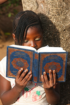 Young girl reading the Koran, Lome, Togo, West Africa, Africa