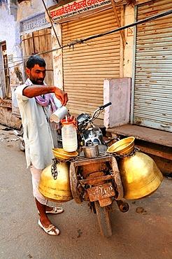 Milk collector carrying milk-churns on his motorbike, Pushkar, Rajasthan, India, Asia