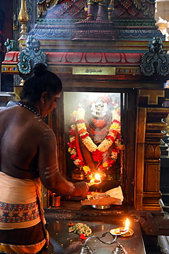 Priest with an arthi (lighted camphor) performing morning puja ceremony, Sri Thendayuthapani Hindu Temple (Chettiars' Temple), Singapore, Southeast Asia, Asia