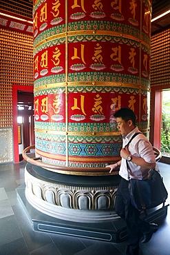 Worshipper and Viarocana Buddhist prayer wheel, Buddha Tooth Relic Temple in Chinatown, Singapore, Southeast Asia, Asia