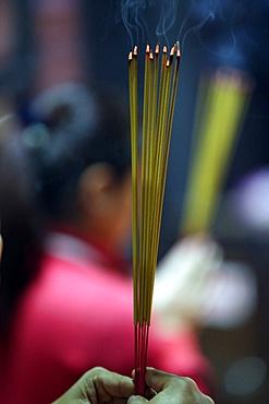 Worshipper burning incense sticks, Taoist temple. Jade Emperore pagoda (Chua Phuoc Hai), Ho Chi Minh City, Vietnam, Indochina, Southeast Asia, Asia