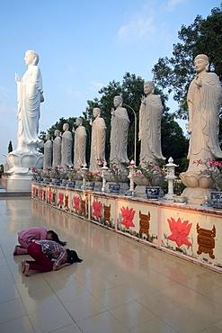 Woman praying in front of Buddha Amitabha statues, Dai Tong Lam Tu Buddhist Temple, Ba Ria, Vietnam, Indochina, Southeast Asia, Asia