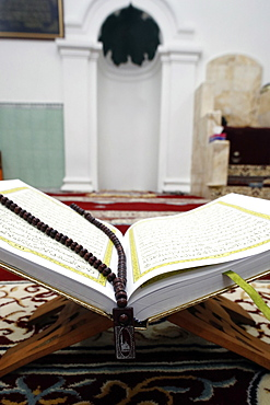An open Holy Quran and a Muslim prayer beads on wood stand with mihrab in background, Hanoi, Vietnam, Indochina, Southeast Asia, Asia